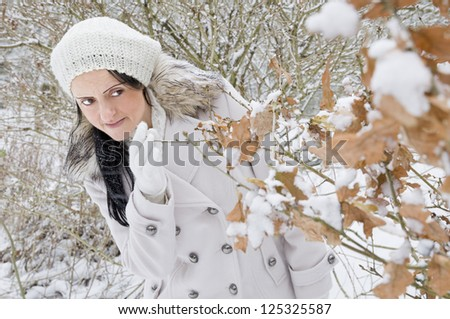 woman hiding behind tree in snow covered woodland - stock photo