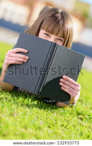 Woman Hiding Face With Book, Outdoors - stock photo