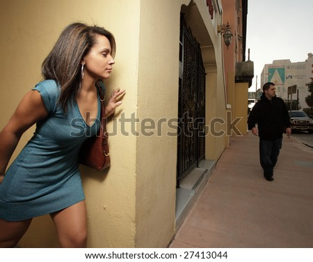 Woman hiding from a thug in the city - stock photo