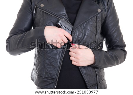 woman hiding gun in leather jacket isolated on white background - stock photo