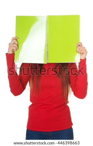 Woman hiding her face behind a notebook. - stock photo