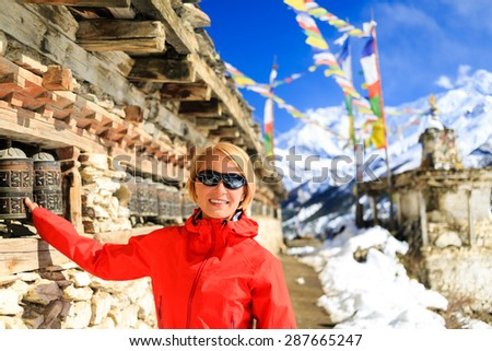 Woman hiker and prayer wheel in Himalaya Mountains, Nepal. Hiking and trekking in white winter nature for healthy lifestyle in beautiful inspirational mountain landscape. - stock photo