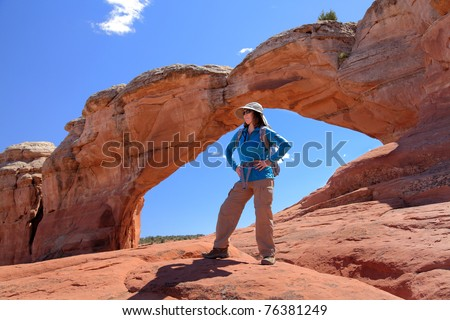 Woman hiker conquers Arches National Park - stock photo