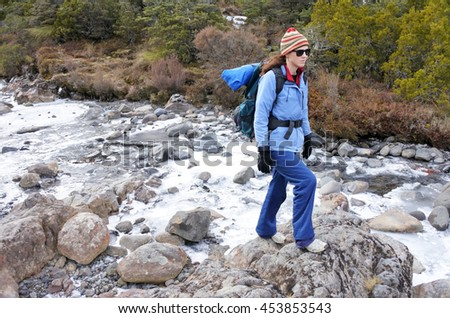 Woman hiker crossing a frozen stream in Tongariro National Park rain forest  in the North Island of New Zealand. Travel concept copy space - stock photo