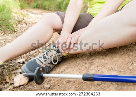 Woman hiker feet tapping in pain due to ankle injury - stock photo