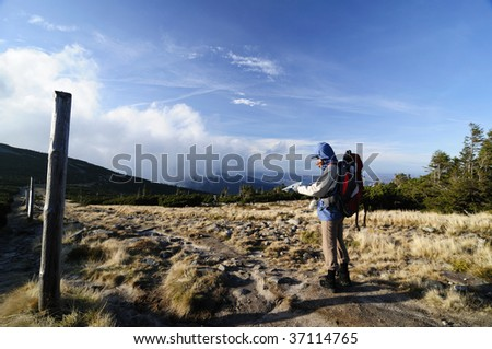 Woman hiker mountain to read a map - stock photo