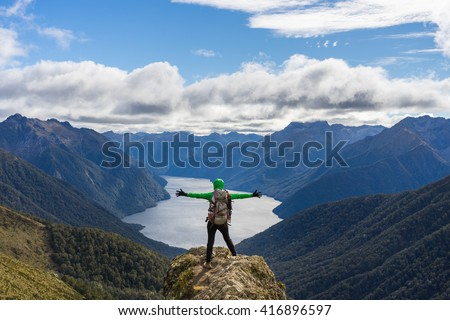 Woman hiker on mountain cliff. Kepler Track, New Zealand - stock photo
