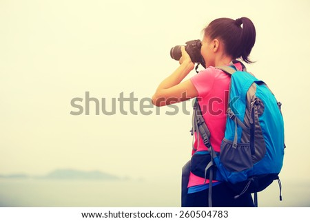 woman hiker photographer taking photo at seaside mountain peak  - stock photo