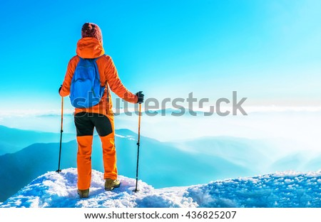 Woman hiker successful on mountain peak summit in winter mountains. Active sport concept. - stock photo