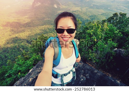 woman hiker taking self photo  at mountain peak - stock photo