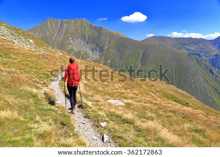 Woman hiker walking on a sunny trail on the mountains - stock photo
