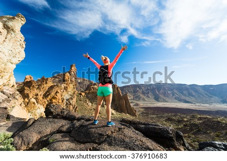 Woman hiker with arms outstretched in mountains. Beauty female runner, hands up and enjoy inspirational landscape on rocky trail footpath on Tenerife, Canary Islands - stock photo