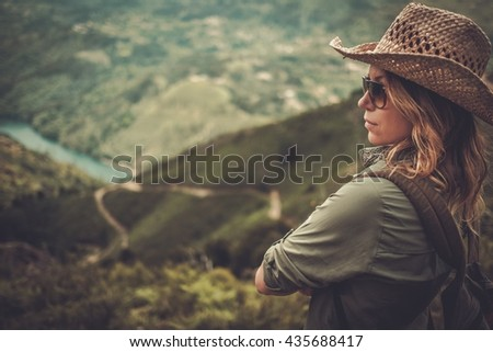 Woman hiker with backpack enjoying amazing valley landscapes on a top of mountain. - stock photo