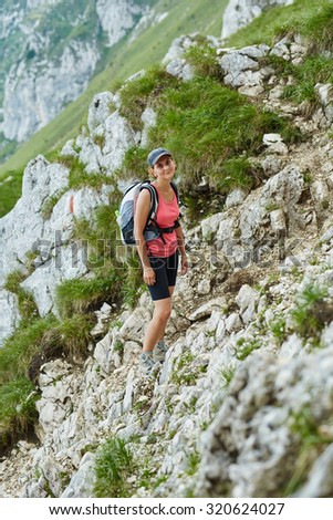 Woman hiker with backpack walking a steep trail in the  mountains - stock photo
