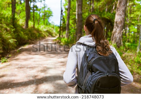 Woman hiker with backpack walking through the forest - stock photo