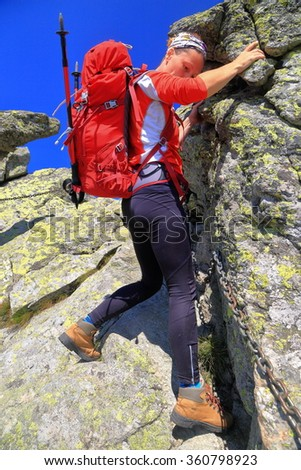 Woman hiker with red backpack traversing along granite cliffs in summer - stock photo