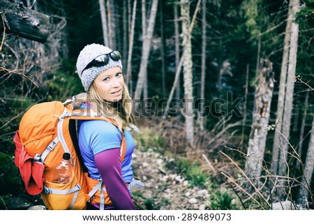 Woman hiking and camping on trail in winter dark dry forest. Recreation and healthy fitness lifestyle outdoors in inspirational nature. Beauty blond hiker camp with backpack looking at camera. - stock photo