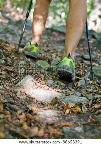 Woman hiking and nordic walking in autumn forest, exercising outdoors - stock photo