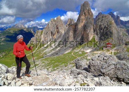 Woman hiking in front of tall spires of Cadini di Misurina and Savio Fonda refuge, Dolomite Alps, Italy - stock photo