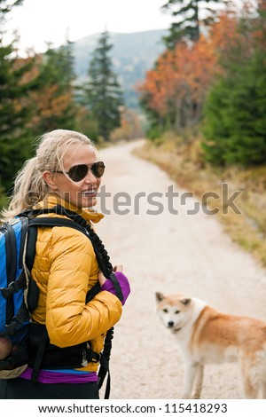 Woman hiking in mountains with akita dog, Karkonosze Mountain Range. Happy smiling hiker on autumn footpath in forest. Young female backpacker walking with canine. - stock photo