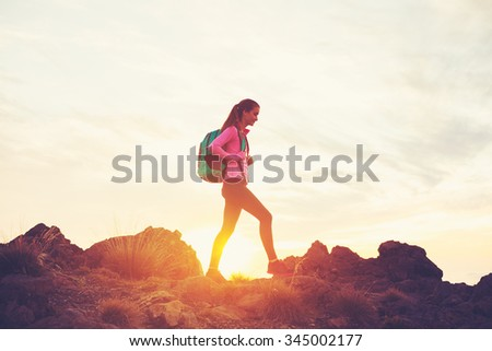 Woman Hiking in the Mountains at Sunset, Adventure Outdoor Active Lifestyle - stock photo