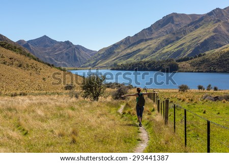 Woman hiking in the mountains on a tourist track at Moke Lake, Otago Region, New Zeraland - stock photo