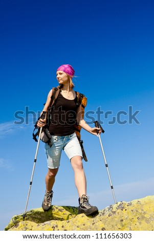 Woman hiking in the mountains, walking and backpacking - stock photo