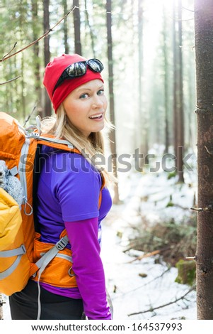 Woman hiking in white winter forest, backlit by morning sunlight rays, recreation and healthy lifestyle outdoors in nature. Beauty blond hiker backpacker looking at camera on sunrise. - stock photo