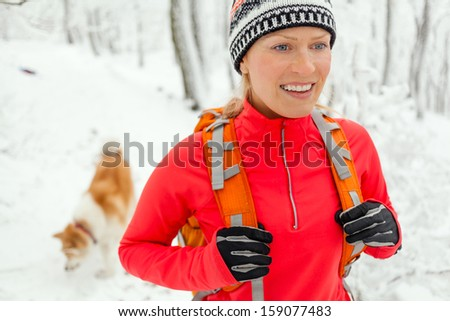 Woman hiking in white winter forest with dog akita inu. Recreation and healthy lifestyle outdoors in nature. Beauty blond hiker walking on snowy footpath. - stock photo
