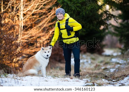Woman hiking in white winter forest woods with akita dog. Recreation fitness and healthy lifestyle outdoors in nature. Motivation and inspirational winter landscape. - stock photo