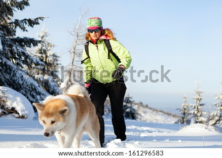 Woman hiking in winter mountains with akita dog. Female hiker walking on white snow with her dog friend, sport and recreation outdoors in nautre, Poland. - stock photo