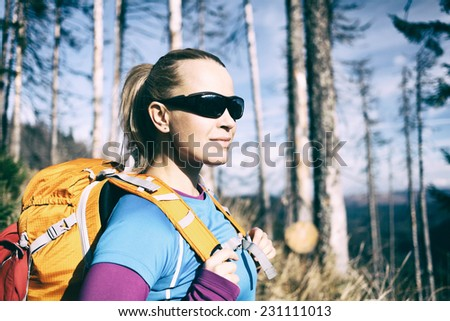 Woman hiking on trail in forest. Vintage retro old style recreation and healthy lifestyle outdoors in nature. Beauty blond hiker with backpack looking at mountains view. - stock photo