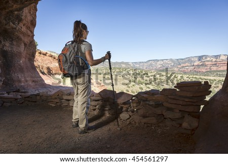 Woman hiking outdoors views landscape from within a cave - stock photo