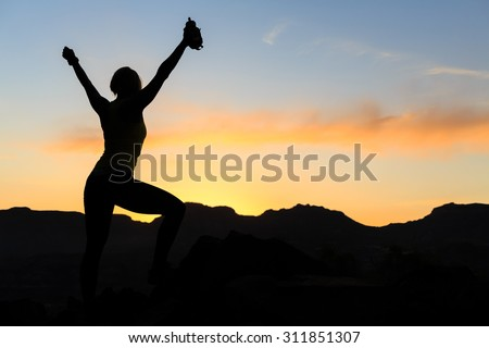 Woman hiking silhouette in mountains, sunset and ocean. Female hiker, climber or trail runner with arms outstretched on mountain top looking at beautiful night sunset inspirational landscape. - stock photo
