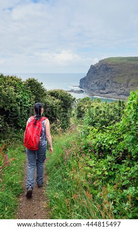 Woman hiking the coastal path near Crackington Haven, Cornwall, England. - stock photo