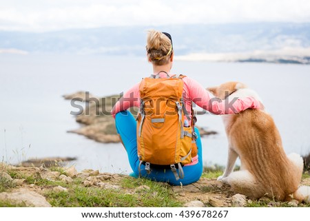 Woman hiking with akita inu dog looking at sea and mountains view. Recreation and healthy lifestyle outdoors in summer nature. Beautiful inspirational landscape. Trekking and activity concept. - stock photo