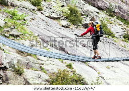 Woman hiking with backpack in mountains, crossing steel suspension bridge, trekking in Corsica France - stock photo