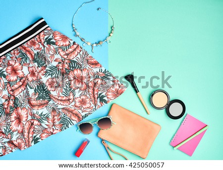 Woman hipster essentials. Fashion urban summer outfit, girl clothes set, cosmetics, makeup accessories. Stylish handbag clutch, pink dress, necklace, sunglasses. Unusual overhead, top view on blue - stock photo