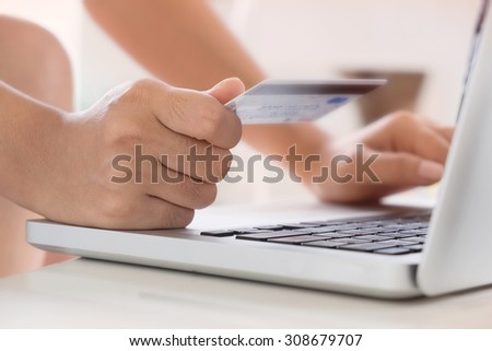 Woman hold Credit Card on laptop waiting for online shopping - stock photo