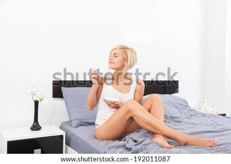 woman hold cup of coffee smell closed eyes dream on bed, young blond girl happy smile morning bedroom home - stock photo