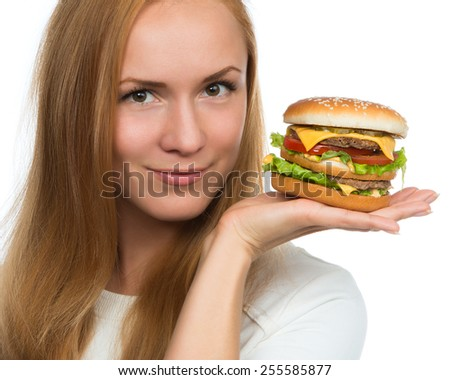 Woman hold tasty unhealthy burger sandwich with cheese salad tomatoes slice and beef in hands hungry getting ready to eat isolated on a white background Fast food concept - stock photo
