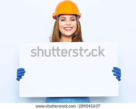 Woman hold white blank business board dressed in builder uniform. Smiling female model.  blue coveralls, glow. - stock photo