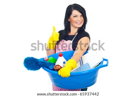Woman holding a basin with brush and cleaning products and giving thumbs up with hands in gloves - stock photo