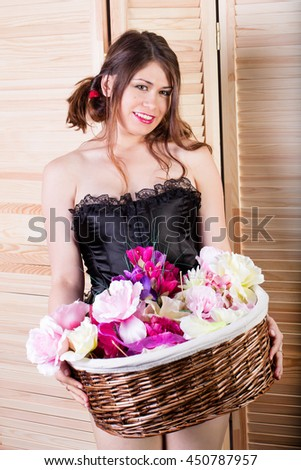 Woman  holding a basket of flowers.  - stock photo