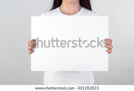 Woman holding a blank A3 poster - stock photo