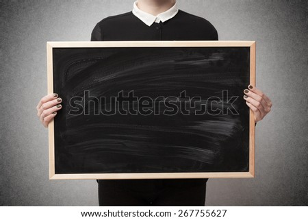 Woman holding a blank blackboard with space for text - stock photo
