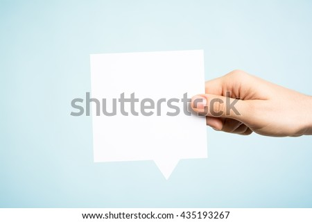 Woman holding a blank paper speech bubble on blue background - stock photo