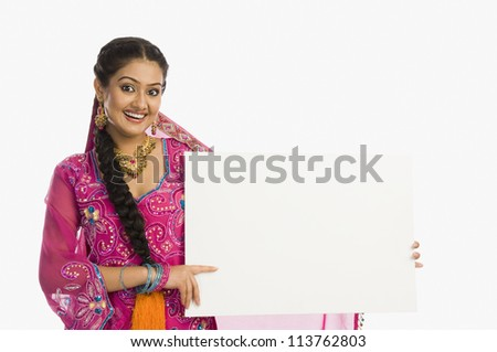 Woman holding a blank placard and smiling - stock photo