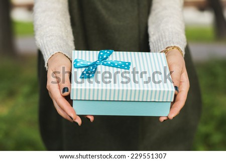 Woman holding a blue gift box in autumn background - stock photo