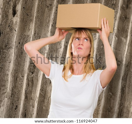 woman holding a box on her head against a grunge background - stock photo